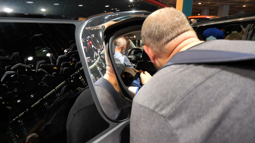 citroen : PARIS, FRANCE - OCT 4, 2018: Male curious customer admiring the interior of the new electric Citroen Car at  exhibition Mondial Paris Motor Show,