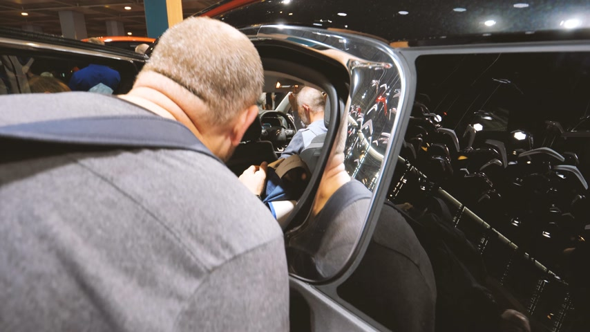 melez : PARIS, FRANCE - OCT 4, 2018: Rear view of male curious customer admiring the interior of the new electric Citroen Car at  exhibition Mondial Paris Motor Show,