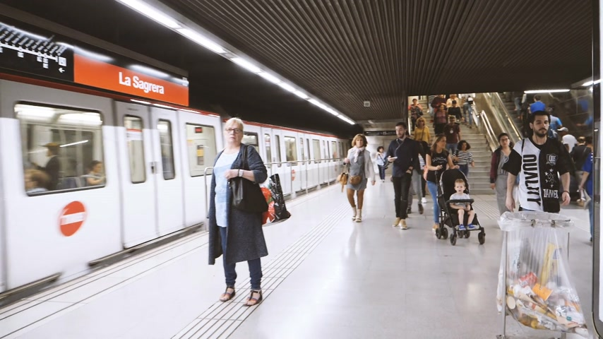 entry : BARCELONA, SPAIN - CIRCA 2018: People walking inside La Sagrera metropolitan subway station commuting to the exit near the fast passing train