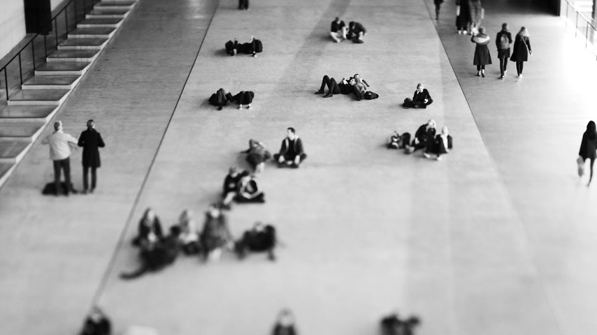 binnenstad : LONDON, UNITED KINGDOM - CIRCA 2018: Visitors enjoying their rest near the entrance at the Tate Modern through the great void of Turbine Hall, the former engine house of the power station the museum used to be - black and white