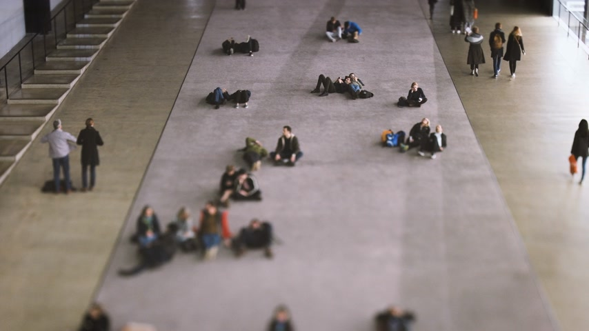 tilt shift : LONDON, UNITED KINGDOM - CIRCA 2018: Visitors enjoying their rest near the entrance at the Tate Modern through the great void of Turbine Hall, the former engine house of the power station the museum used to be