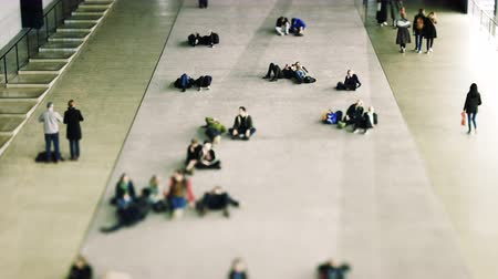 binnenstad : LONDON, UNITED KINGDOM - CIRCA 2018: Cinematic visitors enjoying their rest near the entrance at the Tate Modern through the great void of Turbine Hall, the former engine house of the power station the museum used to be Stock Footage