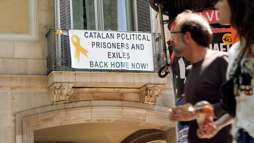 disagreement : BARCELONA, SPAIN - CIRCA 2018: People walking on the Rambla dels Estudis with banner placard on house stating Catalan political prisoners and exiles back home now! - slow motion slowmotion