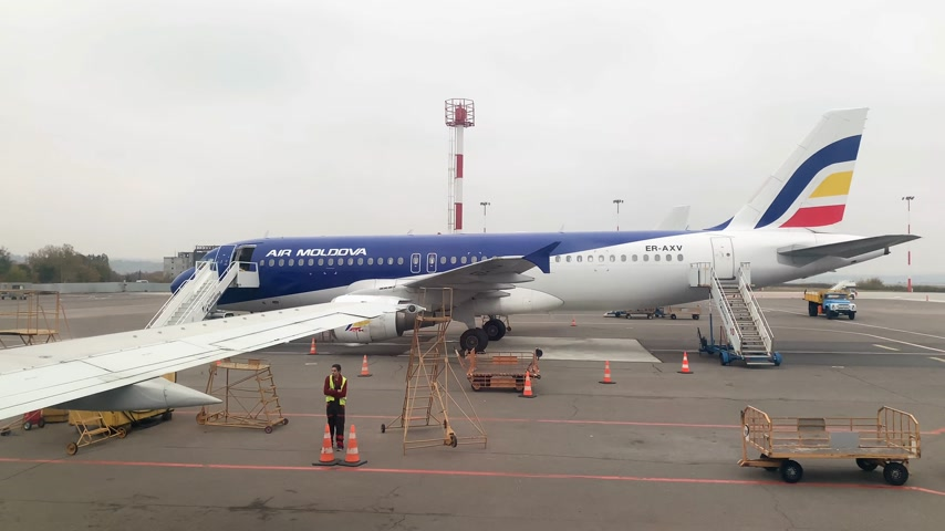 seçkinler : CHISINAU, MOLDOVA - CIRCA 2018: ER-AXV - Airbus A320-211 operated by Air Moldova on tarmac in Chisinau International Airport with crew preparing to load unload the plane