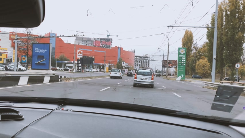 poverty city : CHISINAU, MOLDOVA - NOV 2018: Driver POV on Dacia Boulevard with the famous Shopping MallDova mall on the left, Rompetrol and Bemol gas stations on both sides