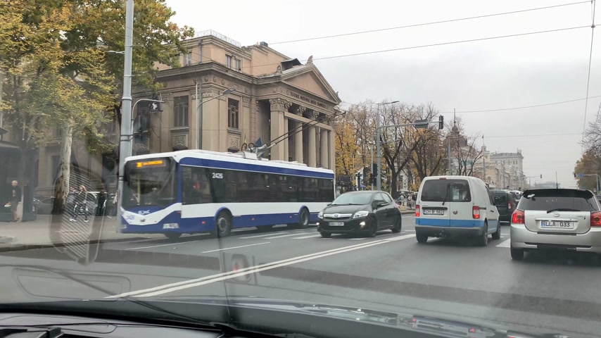 poverty city : CHISINAU, MOLDOVA - NOV 2018: Driver POV on the Stefan cel MAre avenue with Mihai Eminescu National Drama Theater building on the left and people crossing street cars driving