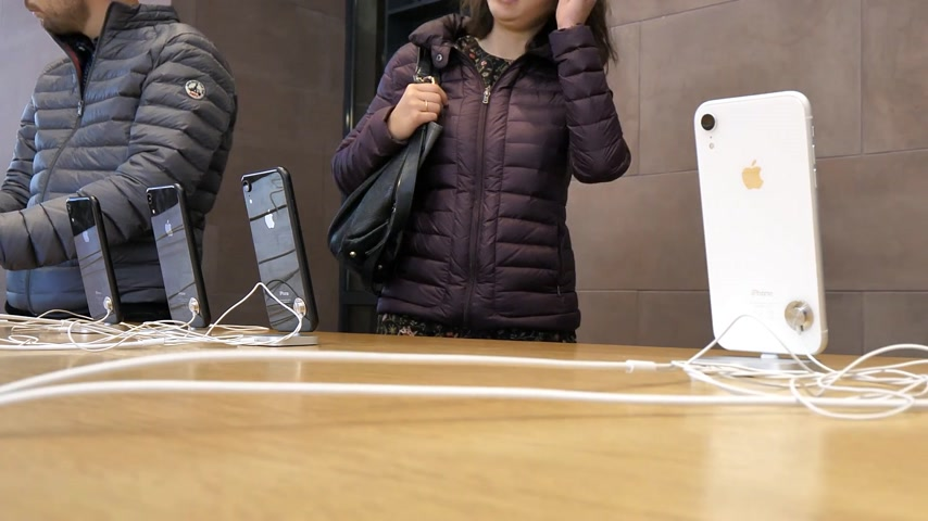 sto : PARIS, FRANCE - NOV 2018: Apple Store with row of new Apple iPhone XR colorful smartphones time -lapse fast motion with customers choosing new telephones
