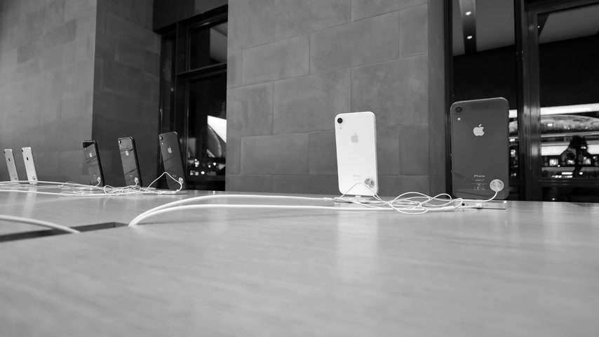 sto : PARIS, FRANCE - NOV 2018: Apple Store with row of new Apple iPhone XR colorful smartphones - black and white footage