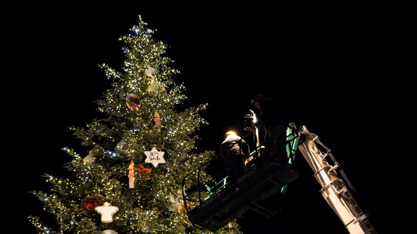 telescopic : STRASBOURG,  FRANCE - CIRCA 2018: Team working on the top of  telescopic crane in central Place Kleber decorating the Christmas Tree with toys before the winter holiday annual market time lapse, fast motion