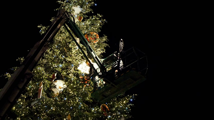 baixo ângulo : STRASBOURG, FRANCE - CIRCA 2018: Low angle view of people on top of telescopic crane in central Place Kleber decorating the Christmas Tree with toys before the winter holiday annual market - working at night