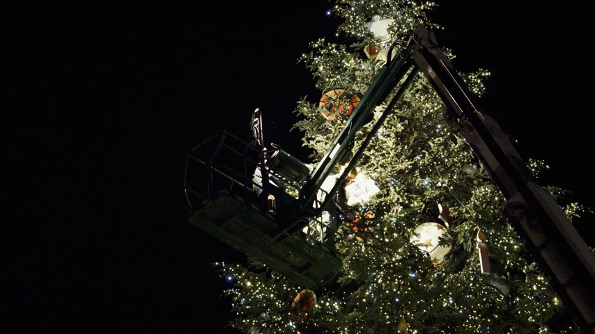 adwent : STRASBOURG, FRANCE - CIRCA 2018: Workers on top of telescopic crane in central Place Kleber decorating the Christmas Tree with toys before the winter holiday annual market - working at night Wideo