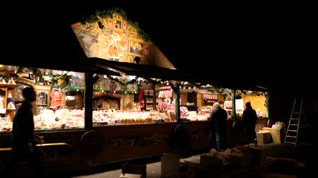 arranging : STRASBOURG, FRANCE - CIRCA 2018: Owner arranging the Christmas market stalls with souvenir a day before the official launch of annual Strasbourg Christmas market in Place Broglie