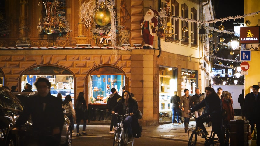 pintado : STRASBOURG, FRANCE - CIRCA 2018:Pedestrian walking commuting on bikes of the Christian Cafe pastry shop in central Strasbourg with large group of people walking in the evening