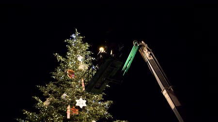 telescopic : STRASBOURG,  FRANCE - CIRCA 2018: Team working on the top of  telescopic crane in central Place Kleber decorating the Christmas Tree with toys before the winter holiday annual market