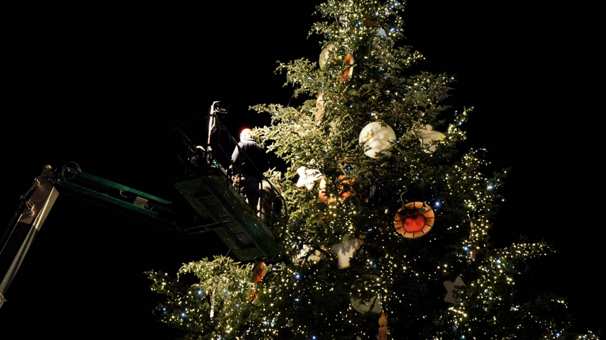 telescopic : STRASBOURG,  FRANCE - CIRCA 2018: Workers working on the top of  telescopic crane in central Place Kleber decorating the Christmas Tree with toys before the winter holiday annual market