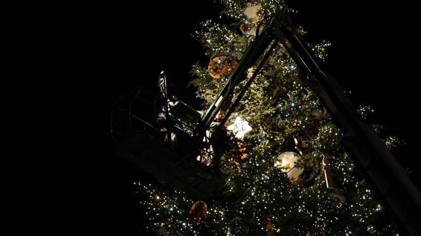 telescopic : STRASBOURG, FRANCE - CIRCA 2018: People on top of telescopic crane in central Place Kleber decorating the Christmas Tree with toys before the winter holiday annual market - working at night