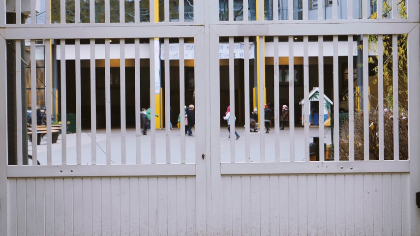 parisli : STRASBOURG, FRANCE - CIRCA 2018: View through the gate at kids playing in the yeard of Lycee prive Sainte-Clotilde lyceum in Strasbourg on a cold winter day