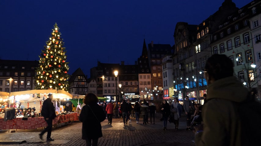 elzas : STRASBOURG, FRANCE - CIRCA 2018: Pan over Evening shot of people visiting the food market in central Place Kleber during the Christmas Market with large fir tree illuminated in the background