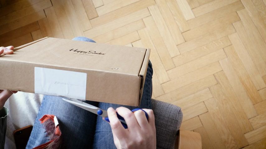 human foot : PARIS, FRANCE - CIRCA 2018: Overhead view of woman unboxing warm socks made by Swedish Brand Happy Socks - online shopping gift receiving Stock Footage