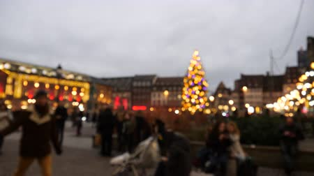 alsatian : Defocused view of the beautiful illuminated Strasbourg Christmas Market in central square of Place Kleber with silhouettes of people admiring the illuminations, having fun in France