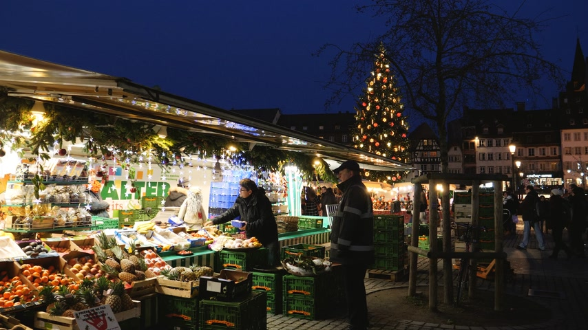 headwear : STRASBOURG, FRANCE - CIRCA 2018: Evening shot of people visiting the food market in central Place Kleber during the Christmas Market with large fir tree illuminated in the background