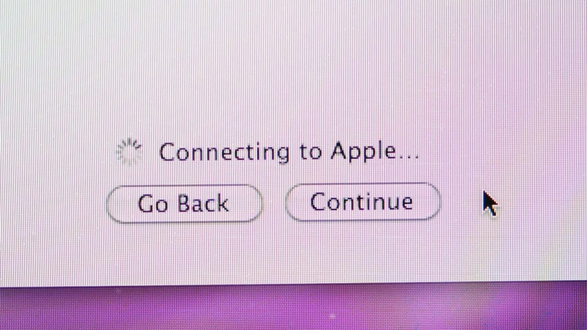 apple sign : CALIFORNIA, UNITED STATES - CIRCA 2014: Apple Computers new desktop computer iMac with Connecting to Apple message and go back and continue buttons and mouse pointer during setup