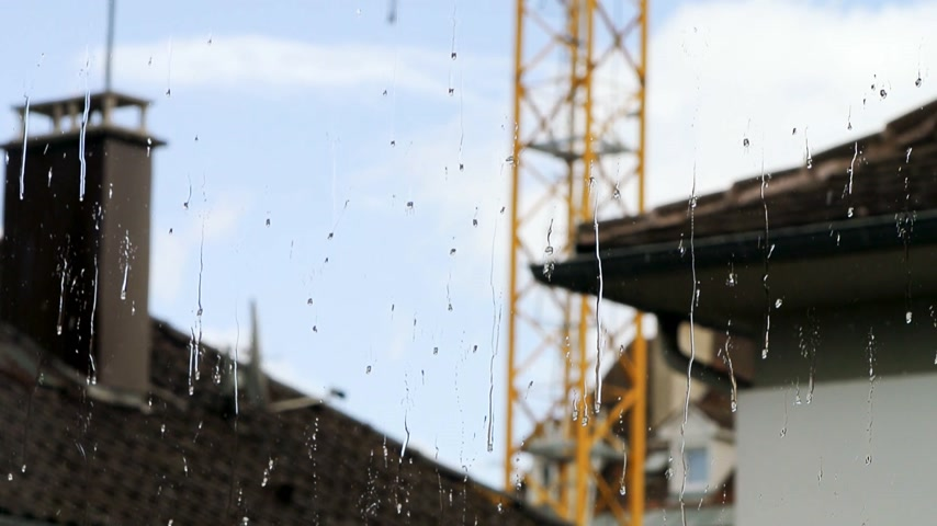 задумчивый : Rain drops on a clean window with houses and construction crane in background Стоковые видеозаписи