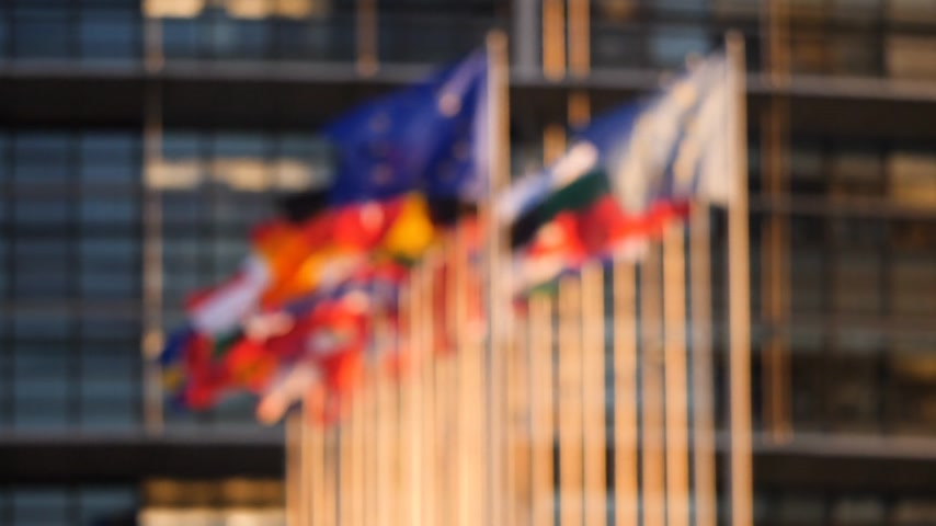 helyettes : Defocused cinematic slow motion over all flags of European Union member states on a warm sunny day in front of European parliament