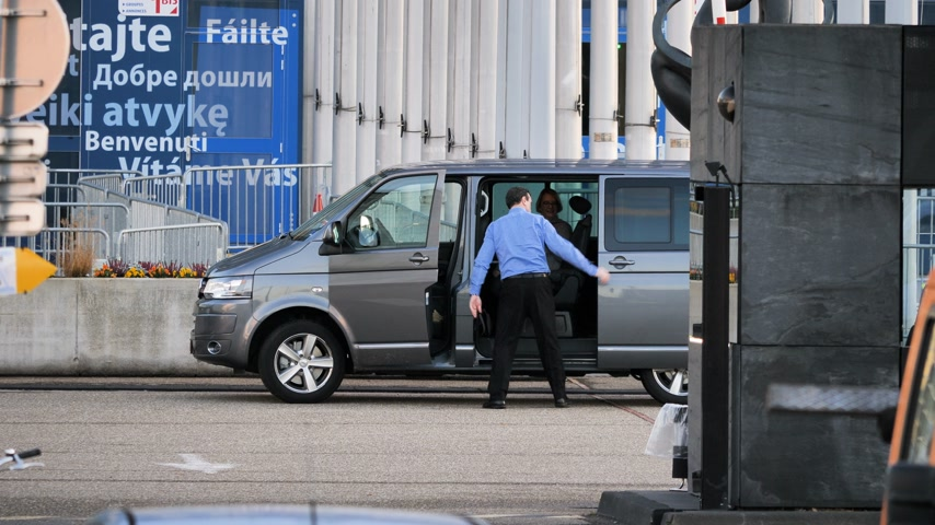 car rental : STRASBOURG, FRANCE - CIRCA 2018: Driver helping MEPs parliamentarians visitor guest entering Volkswagen van leaving the European Parliament during the plenary session Stock Footage