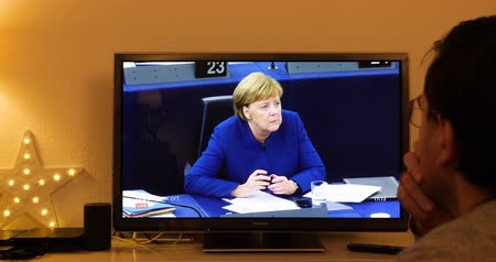 helyettes : STRASBOURG, FRANCE - NOV 13, 2018: Man watching Phoenix German TV broadcasting live German Chancellor Angela Merkel debating the future of Europe with members of European Parliament - question asked