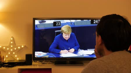 helyettes : STRASBOURG, FRANCE - NOV 13, 2018: Man watching Phoenix German TV broadcasting live German Chancellor Angela Merkel debating the future of Europe with members of European Parliament - question asked- Stock mozgókép