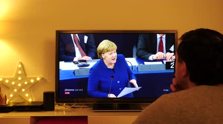 helyettes : STRASBOURG, FRANCE - NOV 13, 2018: Man watching Phoenix German TV broadcasting live German Chancellor Angela Merkel speech about future of Europe with members of European Parliament
