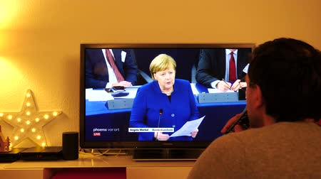 bürokrasi : STRASBOURG, FRANCE - NOV 13, 2018: Man watching Phoenix German TV broadcasting live German Chancellor Angela Merkel debating the future of Europe with members of European Parliament