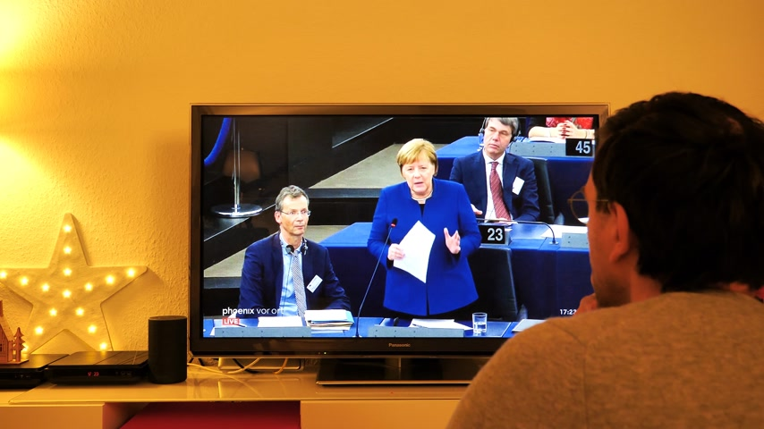 helyettes : STRASBOURG, FRANCE - NOV 13, 2018: Man watching Phoenix German TV broadcasting live German Chancellor Angela Merkel answering questions from MEPs about the future of Europe in Eu Parliament