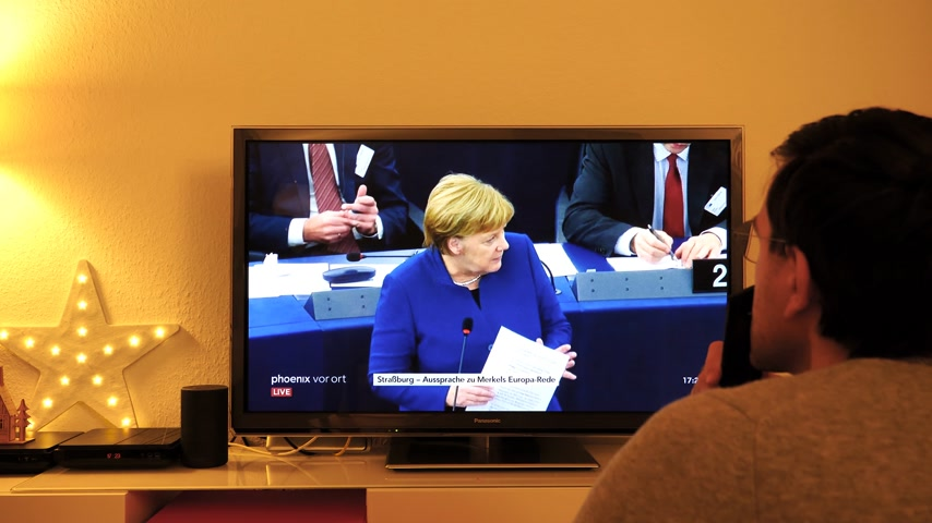 chancellor : STRASBOURG, FRANCE - NOV 13, 2018: Man watching Phoenix German TV broadcasting live German Chancellor Angela Merkel explaining her vision about future of Europe with members of European Parliament Stock Footage