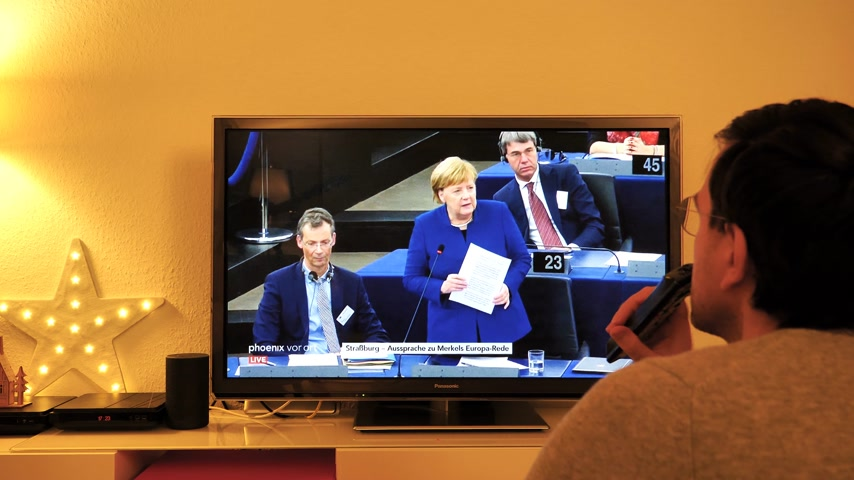 helyettes : STRASBOURG, FRANCE - NOV 13, 2018: Man watching Phoenix German TV broadcasting live German Chancellor Angela Merkel explaining her vision about the future of Europe in European Parliament