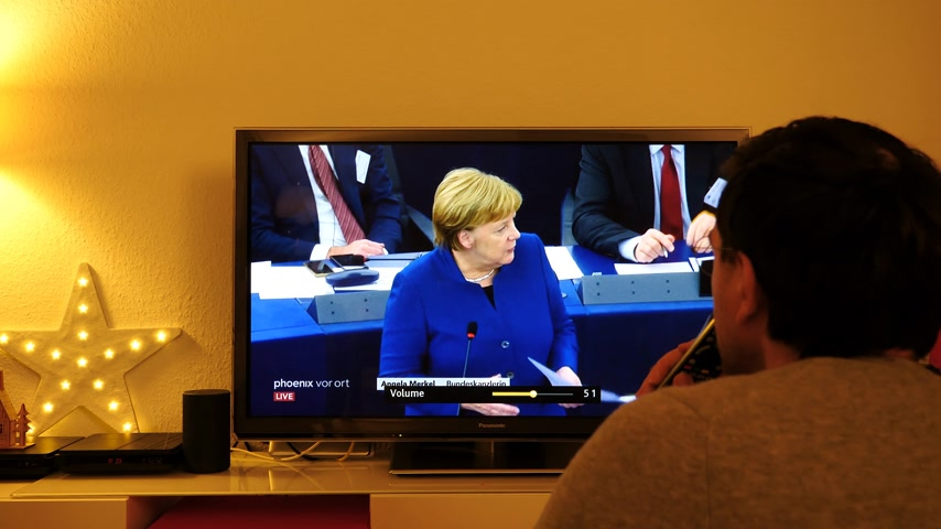 helyettes : STRASBOURG, FRANCE - NOV 13, 2018: Time lapse fast motion of man watching Phoenix German TV broadcasting live German Chancellor Angela Merkel debating the future of Europe in European Parliament