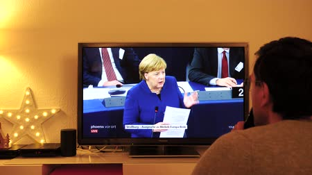 helyettes : STRASBOURG, FRANCE - NOV 13, 2018: Man following Phoenix German TV broadcasting live German Chancellor Angela Merkel speech about the future of Europe with members of European Parliament