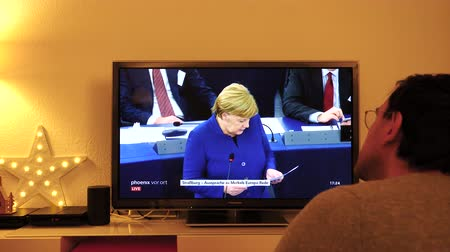 parlamento : STRASBOURG, FRANCE - NOV 13, 2018: Man watching Phoenix German TV broadcasting live German Chancellor Angela Merkel debating the future of Europe with members of European Parliament