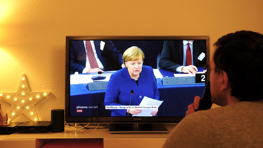 helyettes : STRASBOURG, FRANCE - NOV 13, 2018: Man watching German TV broadcasting live German Chancellor Angela Merkel debating the future of Europe with members of European Parliament