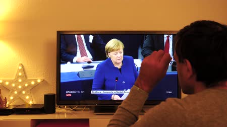 helyettes : STRASBOURG, FRANCE - NOV 13, 2018: Man watching Phoenix German TV broadcasting live German Chancellor Angela Merkel talking about the future of Europe with members of European Parliament