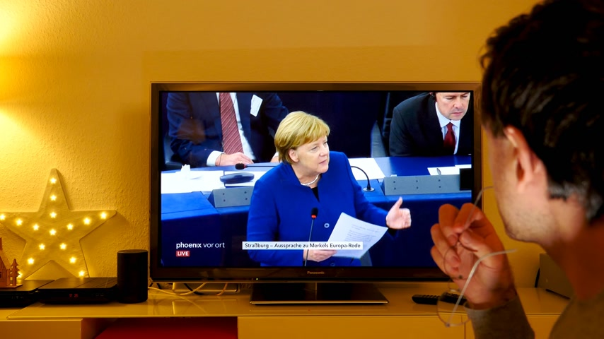 helyettes : STRASBOURG, FRANCE - NOV 13, 2018: Man following Phoenix German TV broadcasting live German Chancellor Angela Merkel talking about the future of Europe with members of European Parliament Stock mozgókép