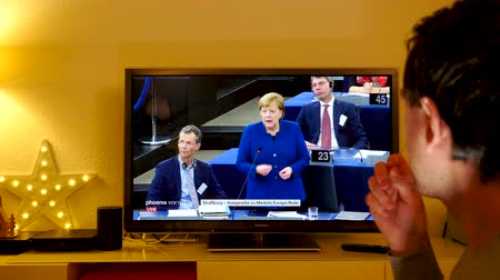 helyettes : STRASBOURG, FRANCE - NOV 13, 2018: Man watching Phoenix German TV broadcasting live German Chancellor Angela Merkel explaining her vision about the future of Europe