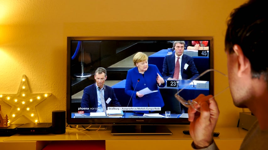 helyettes : STRASBOURG, FRANCE - NOV 13, 2018: Man listening to Phoenix German TV broadcasting live German Chancellor Angela Merkel debating the future of Europe with members of European Parliament Stock mozgókép