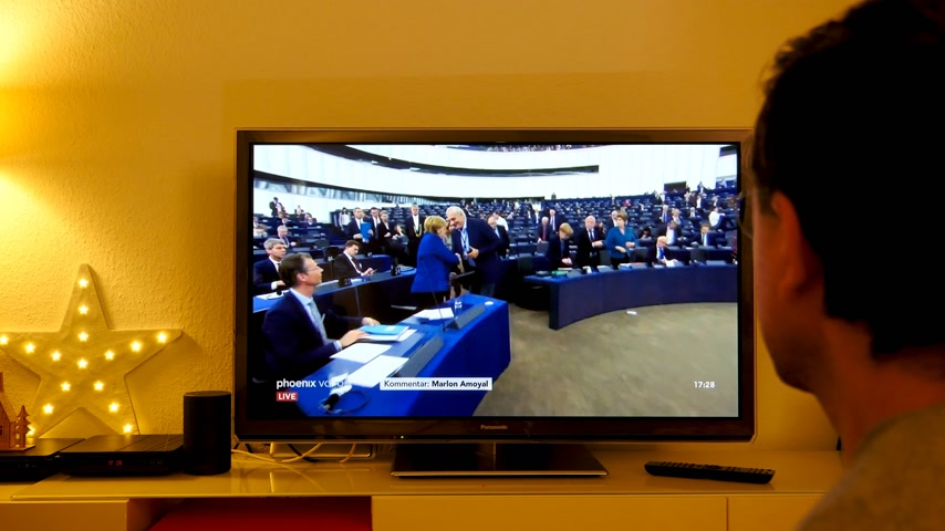 bürokrasi : STRASBOURG, FRANCE - NOV 13, 2018: Man watching Phoenix German TV broadcasting live German Chancellor Angela Merkel after debate the future of Europe with members of European Parliament