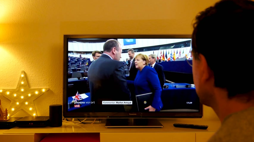 helyettes : STRASBOURG, FRANCE - NOV 13, 2018: Man watching Phoenix German TV broadcasting live German Chancellor Angela Merkel debating the future of Europe with members of European Parliament