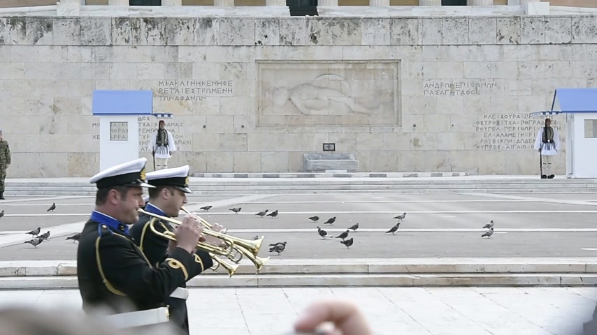 посещающий : ATHENS, GREECE- CIRCA 2018: Traditional Greek music performed by military orchestra marching in front of honor Evzones guard in front of Tomb of the Unknown Soldier at the Parliament Building in Syntagma Square Стоковые видеозаписи