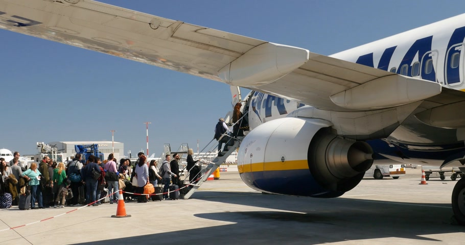 bedrijfsuitje : ATHENE, GRIEKENLAND - CIRCA 2017: Zoom-out van passagiers aan boord van Ryanair Airlines Boeing-vliegtuigen op het Athene International Airport asfalt Athens International Airport Eleutherius Venizelos
