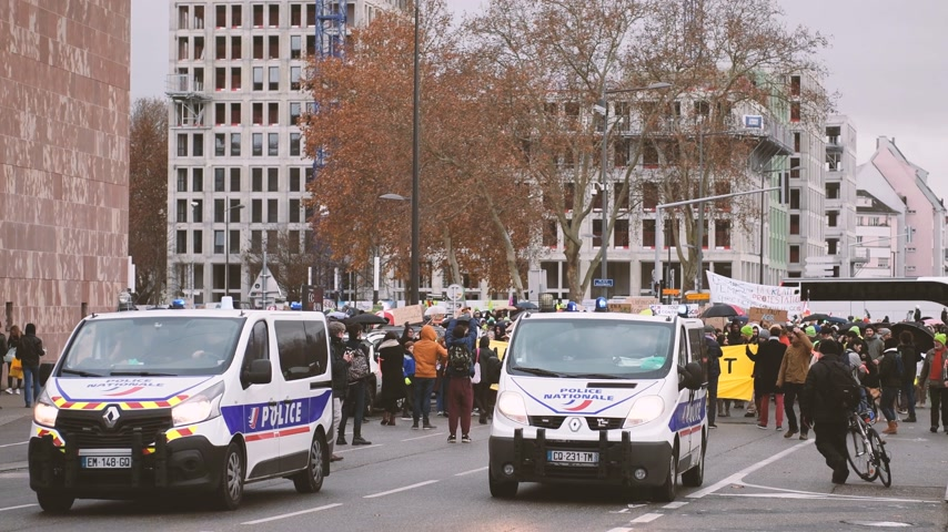 anti macron : STRASBOURG, FRANCE - DEC 8, 2018: Police vans in front of crowd marching in Central Strasbourg at the nationwide protest Marche Pour Le Climate on a rainy day