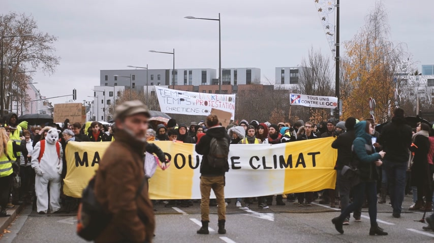 yelek : STRASBOURG, FRANCE - DEC 8, 2018: Crowd of people marching in Central Strasbourg at the nationwide protest Marche Pour Le Climate with large yellow palcard Stok Video